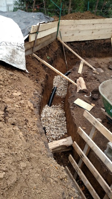 Trench with wheelbarrow-fulls of gravel dumped in.